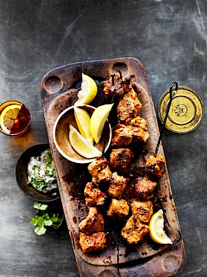 Photograph of Lamb Tandoori on a wooden platter with limes and skewers of meat