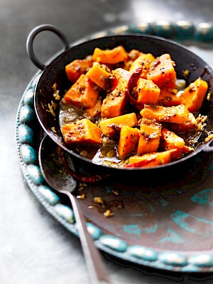 Photograph of a bowl of Bengali butternut squash curry with dried spices and a messy spoon