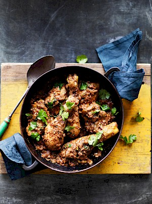 Photograph of Black Chicken Curry with Black Masala Spice Mix in a pan on a table with blue napkins and a yellow board.