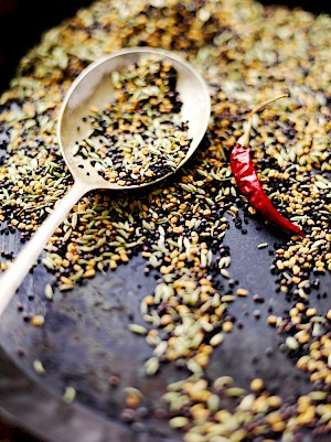 Photograph of dry spices being dry fried in a pan and a spoon with some of the spice mix
