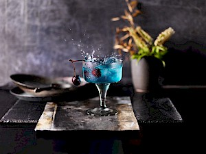 Photograph of a blue cocktail with a red cherry splashing into the cocktail