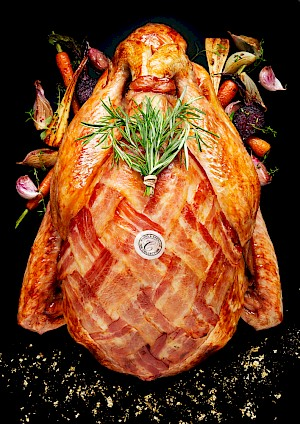 Photograph of M&S Christmas Turkey with roasted vegetable and rosemary garnish