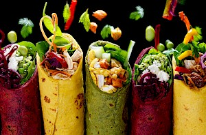 Photograph of Wraps with ingredients falling into them.