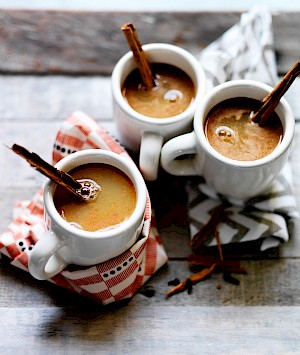 Photograph of hot spiced apple drink with cinnamon sticks stirrers