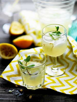 Photograph of Mint and ginger lemonade with mint garnish and squeezed lemons